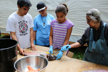 Bea Wilson teaching the youth how to cut salmon in a way that none of the fish is wasted. Photo credit: Brenda Bouzane.